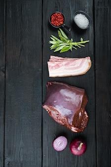 Foie de boeuf cru avec bacon et oignon sur fond de bois noir, mise à plat avec espace de copie.