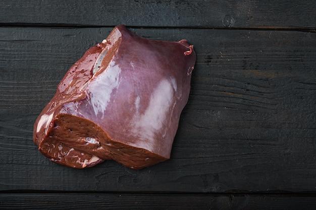 Foie de boeuf cru sur fond de bois noir, mise à plat avec espace de copie.