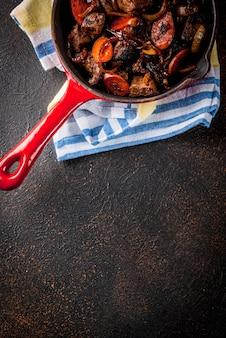 Foie de boeuf rôti ou grillé avec oignon et carotte dans une poêle à frire, vue de dessus de table rouillé foncé