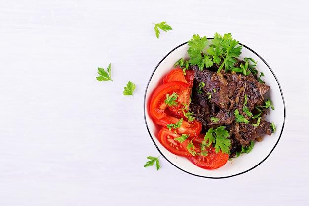 Foie de boeuf rôti ou grillé avec salade d'oignons et tomates
