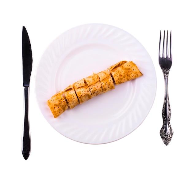 Foie de crêpes délicieux coupé en morceaux sur une plaque blanche avec un couteau et une fourchette en métal