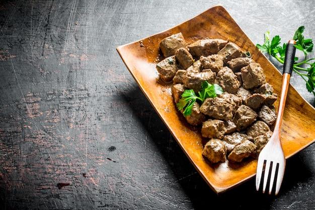Foie frit au persil. sur fond rustique foncé