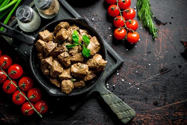 Foie frit aux épices et tomates cerises sur une planche à découper. sur table rustique sombre