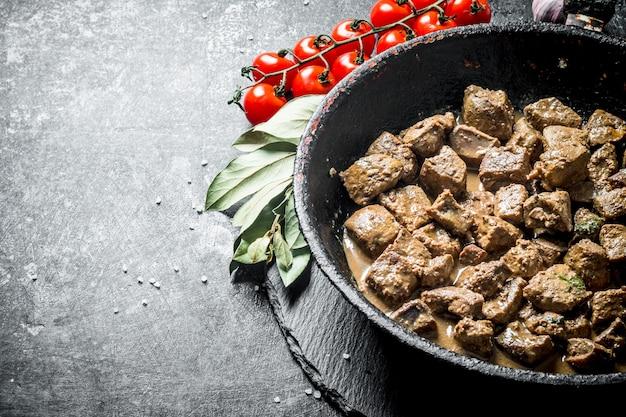Foie frit dans une poêle avec feuille de laurier et tomates. sur fond rustique foncé