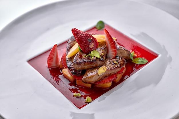 Foie gras en sauce aux fraises avec des morceaux de poire et de fraise sur plaque blanche