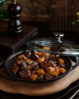 Foie grillé avec pommes de terre carrées dans une assiette noire