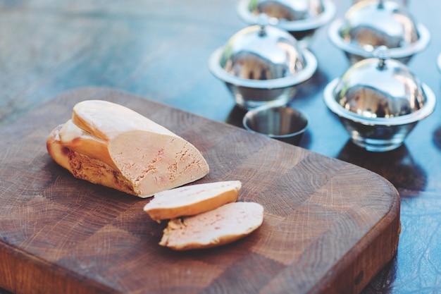 Foie d'oie sur une planche de bois dans le restaurant avant la cuisson.