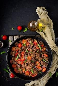 Foie de poulet (abats) aux oignons et tomates dans une poêle en arménien. mise à plat. vue de dessus