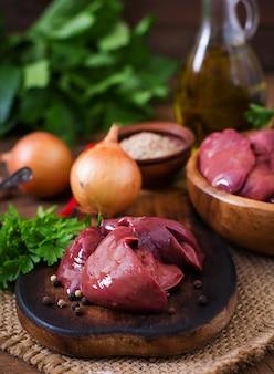 Foie de poulet cru pour cuisiner avec des oignons et des poivrons