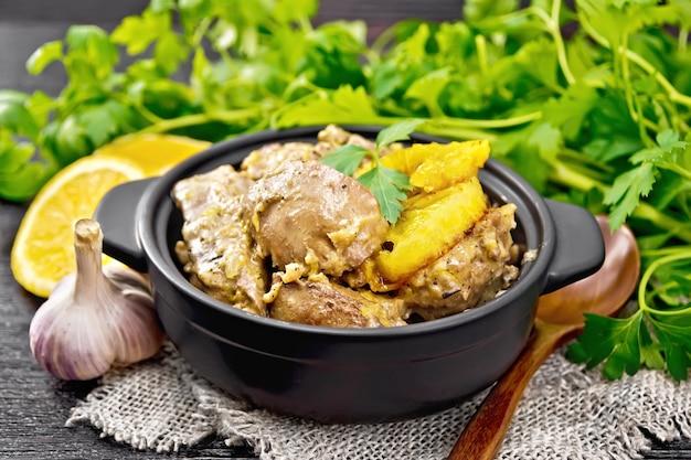 Foie de poulet cuit aux oranges, crème sure, sauce soja et herbes provençales dans une petite casserole sur une serviette en toile de jute