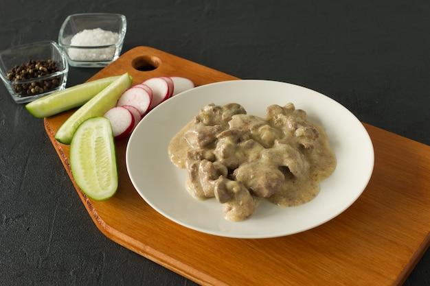 Foie de poulet cuit avec sauce à l'oignon et à la crème sure sur une assiette servie sur un bureau en bois. style rustique.