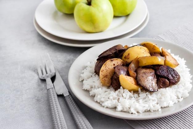 Foie de poulet frit aux pommes servi avec du riz blanc sur une assiette. pommes vertes en surface