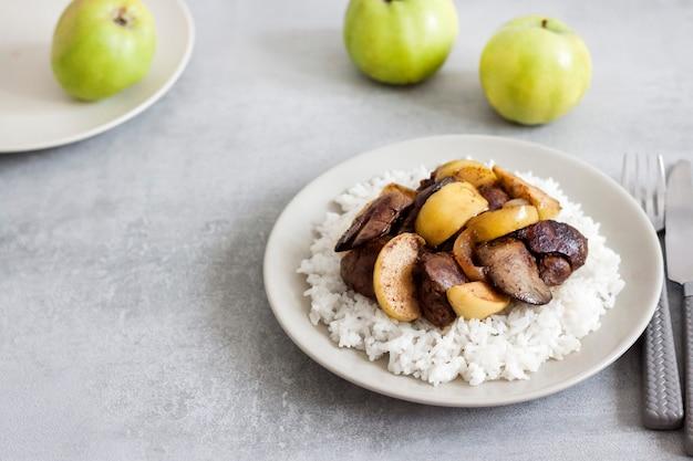 Foie de poulet frit aux pommes servi avec riz blanc sur une assiette