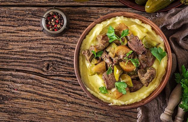 Foie de poulet frit avec pommes, poivrons et oignons avec purée de pommes de terre