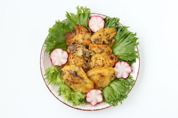 Le foie de poulet en pâte est situé sur une assiette sur fond blanc, vue de dessus