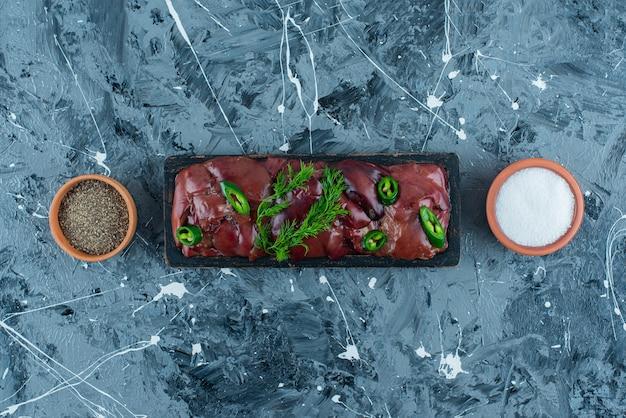 Foies de poulet crus sur une planche à côté de bols d'épices, sur le fond bleu.