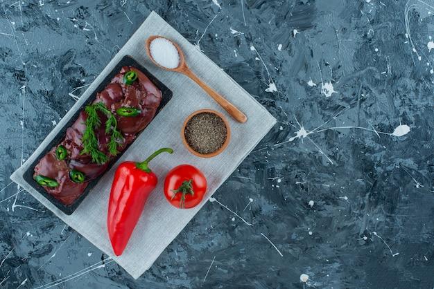 Foies de poulet sur une planche à côté de différents légumes et épices sur la serviette, sur le fond bleu.