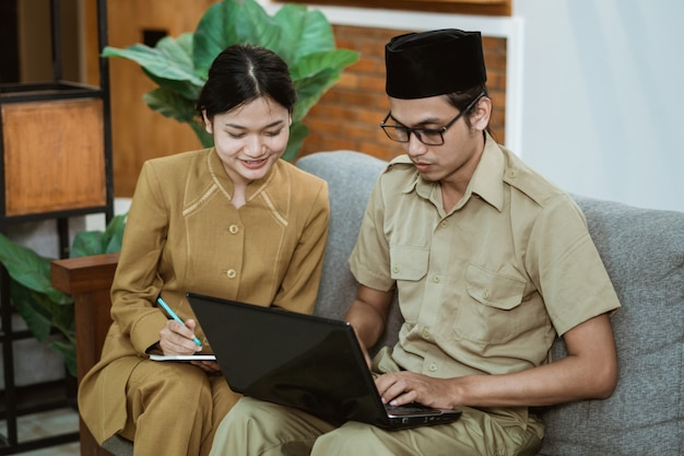 Un fonctionnaire et une assistante en uniforme de fonctionnaire sont assis sur un canapé et travaillent en ligne à l'aide d'un ordinateur portable