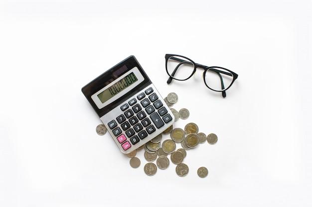 Fond d'affaires. calculs financiers avec calculatrice, pièces de monnaie et lunettes sur un bureau blanc.