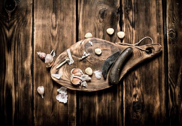 Fond d'ail. l'ail frais sur la vieille planche de bois.