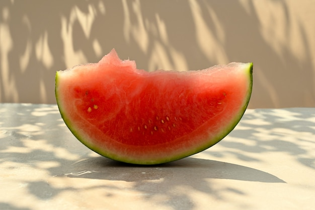 Fond d'aliments d'été. tranche de pastèque mûre sur fond chaud avec des nuances dures et la lumière du soleil.