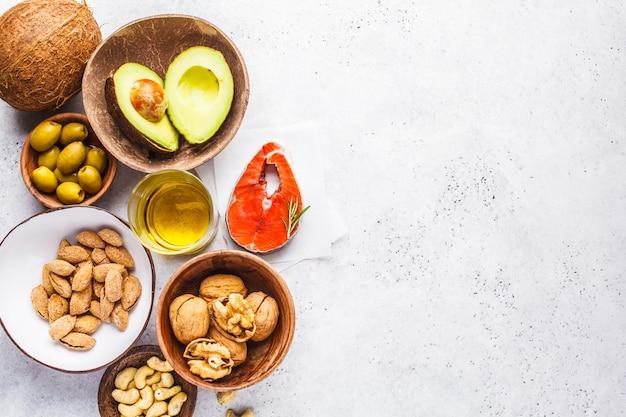 Fond d'aliments gras sains. poisson, noix, huile, olives, avocat sur fond blanc, vue de dessus