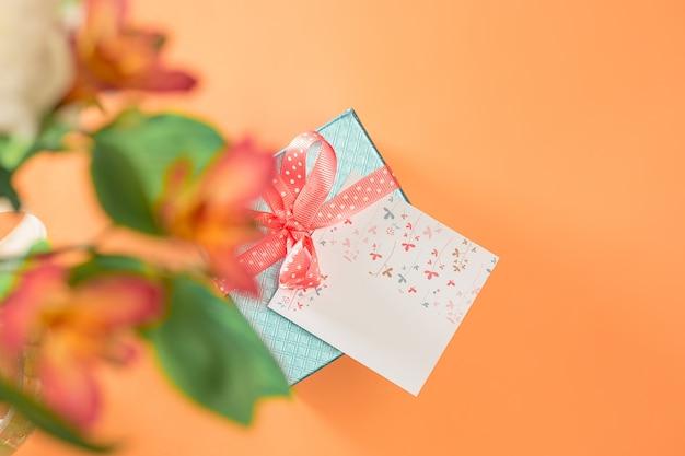 Fond d'amour avec des roses roses, des fleurs, un cadeau sur la table