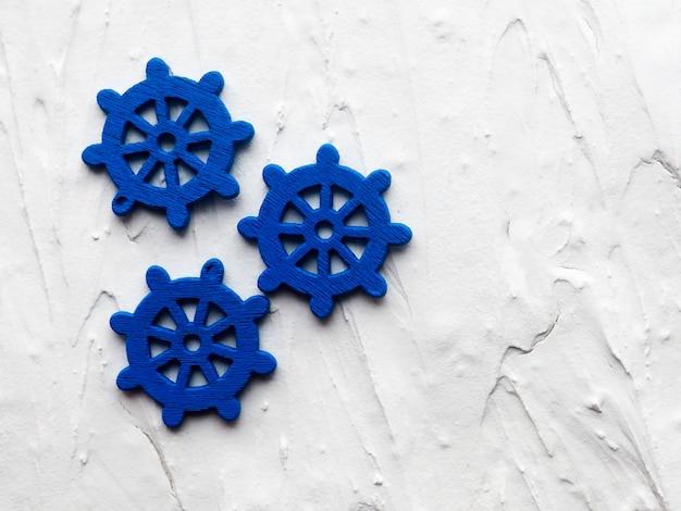 Fond avec des ancres décoratives et des roues sur un fond peint en blanc.