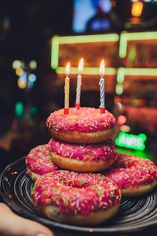 Fond d'anniversaire coloré avec des beignets et des bougies.