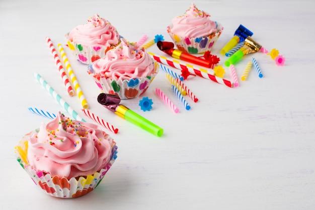 Fond d'anniversaire de petits gâteaux et bougies roses