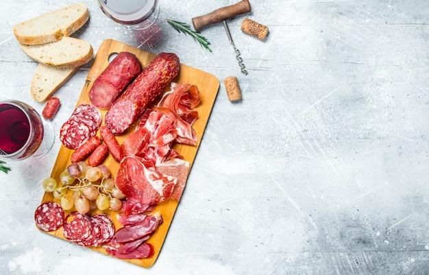 Fond d'antipasto assortiment de collations de viande avec du vin rouge. sur un fond rustique.