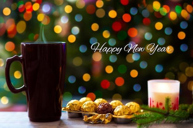 Fond d'arbre de noël avec gerland avec du cacao et des bonbons chocolat chaud avec des bonbons sur