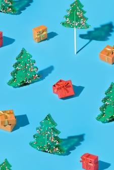 Fond avec des arbres de noël et des coffrets cadeaux sur fond bleu. célébrer le nouvel an et noël. composition minimaliste avec sucettes et cadeaux.