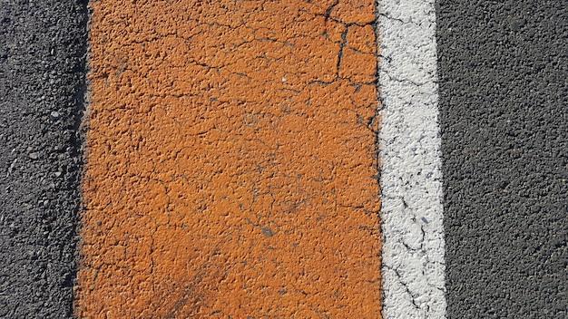 Fond d'asphalte avec des lignes blanches et jaunes.