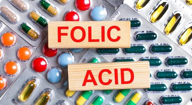 Sur le fond des assiettes multicolores, des blocs de bois avec le texte acide folique. notion médicale.