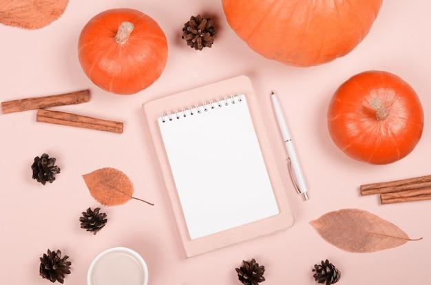 Fond d'automne avec bloc-notes, citrouille orange, cannelle et feuilles sur fond clair