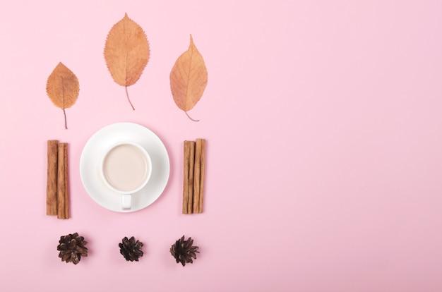 Fond d'automne avec café, cannelle et feuilles sur fond rose