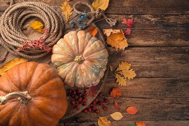 Fond d'automne avec des citrouilles et du feuillage sur un fond marron en bois. vue de dessus, copiez l'espace.
