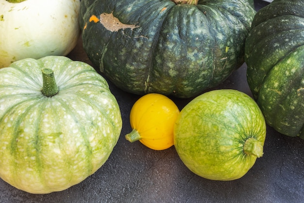 Fond d'automne. citrouilles naturelles d'automne sur fond de schiste noir foncé, papier peint d'octobre ou de septembre changement de saisons concept d'aliments biologiques mûrs fête d'halloween jour de thanksgiving