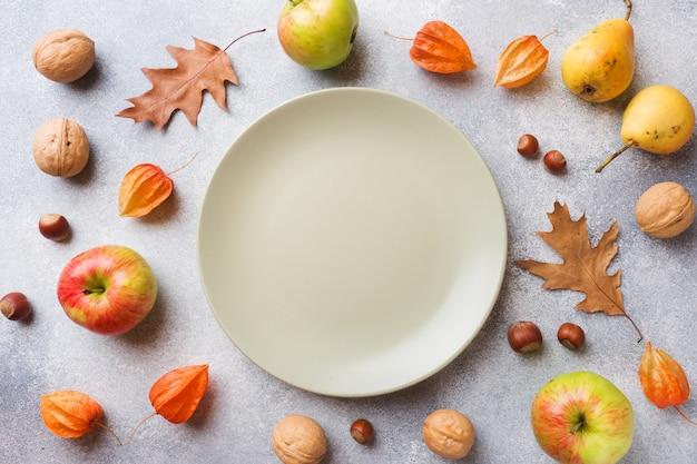 Fond d'automne avec les feuilles jaunes, pommes citrouilles poires et noix