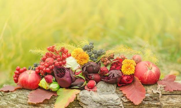 Fond d'automne avec des feuilles jaunes, des pommes et des fleurs.