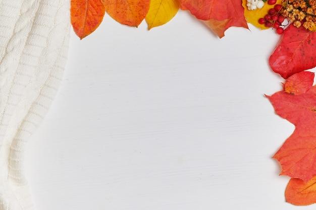 Fond d'automne avec des feuilles jaunes, pull sur fond blanc avec espace de copie.