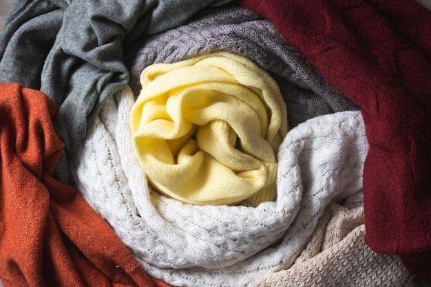 Fond d'automne ou d'hiver avec des pulls chauds pile de vêtements tricotés chauds
