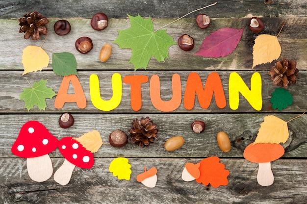 Fond d'automne à la main. mot automne, feuilles, champignons, glands en feutre. châtaignes, cônes et feuilles d'automne sur le vieux fond en bois