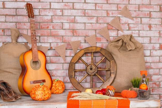 Fond d'automne avec seigle, blé, avec feuilles d'érable jaune, citrouilles, pommes rouges