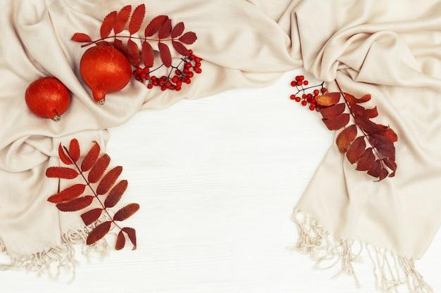 Fond d'automne avec le sorbier laisse la couleur rouge et les sorbiers sur l'écharpe douce de vêtements d'automne pour femme, les pampkins orange sur bois blanc avec copie vue de dessus. mise à plat