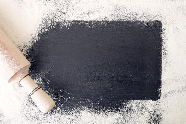 Fond autour du rouleau à pâtisserie et de la farine sur fond noir. vue de dessus. cadre.