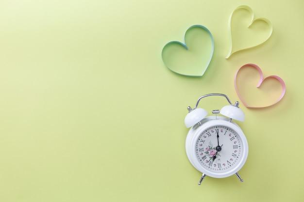 Fond de bannière de la journée mondiale du coeur réveil blanc et symbole du coeur sur fond de table concept médical.