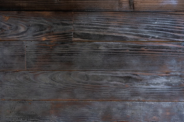 Fond de barbecue. texture de planche de bois brûlé. surface de bois dur rayée brûlée. fumer le fond de planche de bois. texture grunge en bois brûlé