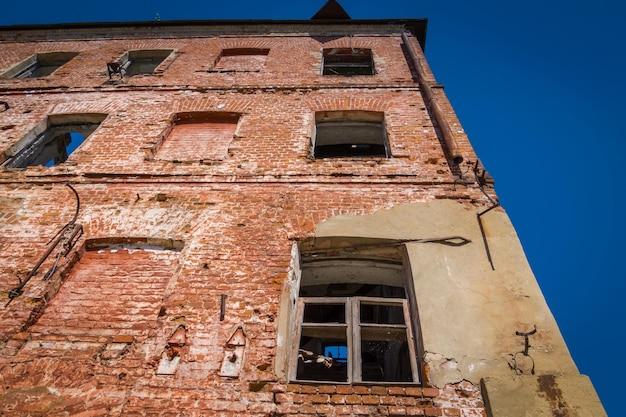 Fond de bâtiment en brique rouge vieux et cassé.